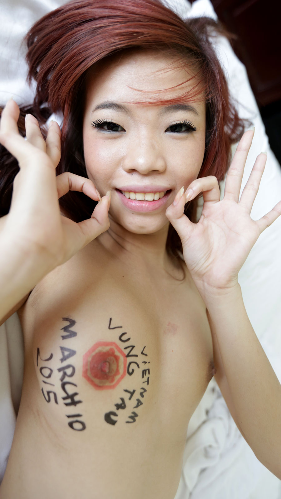 Topless Vietnamese babe striking a pose with exposed tiny tits